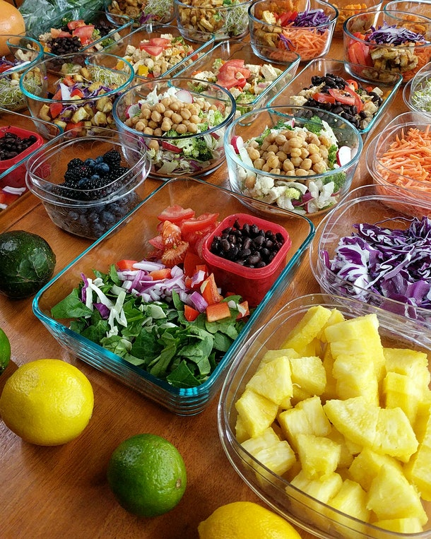 Vegan vegetarian meal prep on wooden table with colorful fruits and vegetables, weekly meal prep spread on table, healthy food prep for the week