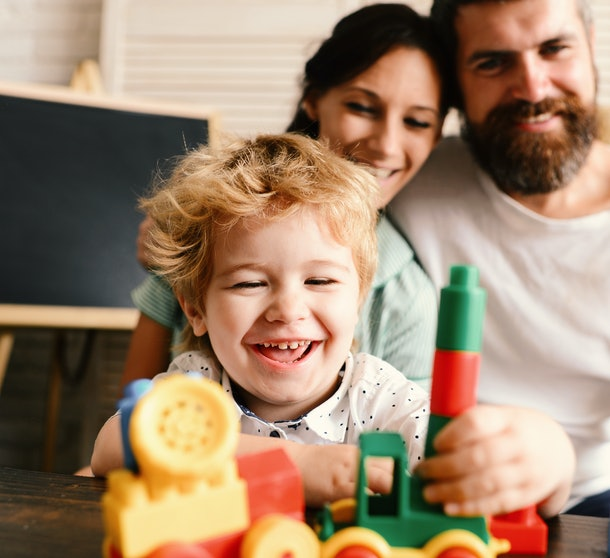 Love and family games concept. Mom, dad and boy on light background build out of toy blocks. Parents watch their son with happy face making brick constructions. Young family spends time in playroom