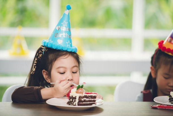 Little Cute Girl Enjoy Eating Cake at School with Friends in Classroom Party