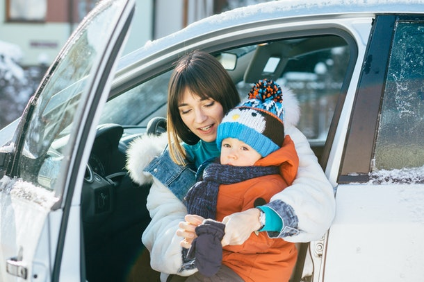 Happy family concept. Young mother on driver's seat of car and trying to wear mittens her cute toddler son in cold winter day. Family wearing bright warm clothes.