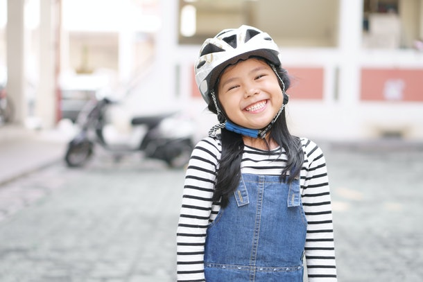 Asian child cute or kid girl wear white motorcycle or bike helmet with happy smiling white teeth for confident and head safety or sport exercise protect on street and road riding or driver travel