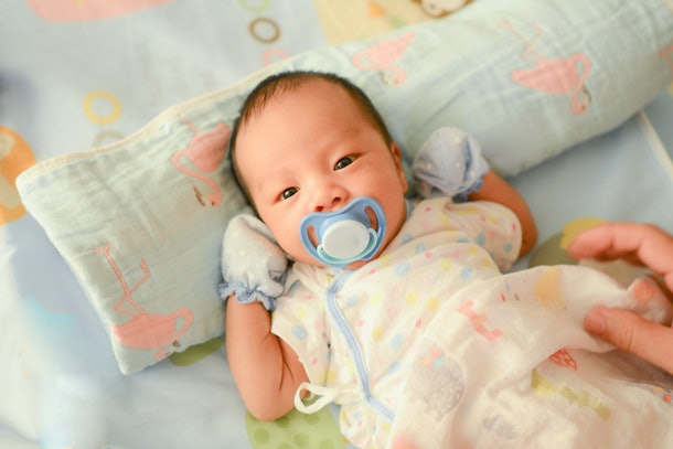 Asian newborn baby boy with a pacifier