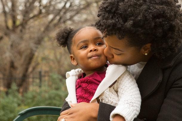 Mother kissing her little girl.