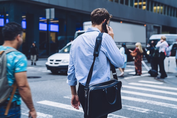 Intelligent man lawyer with briefcase using international roaming internet connection for making business conversation via cellular phone, back view of male economist phoning to operator via app