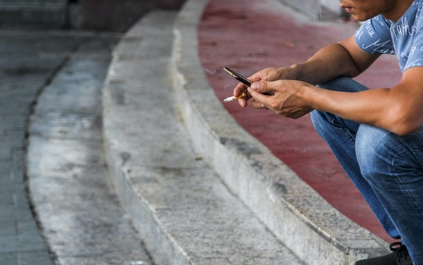 hands of smoking and using phone man