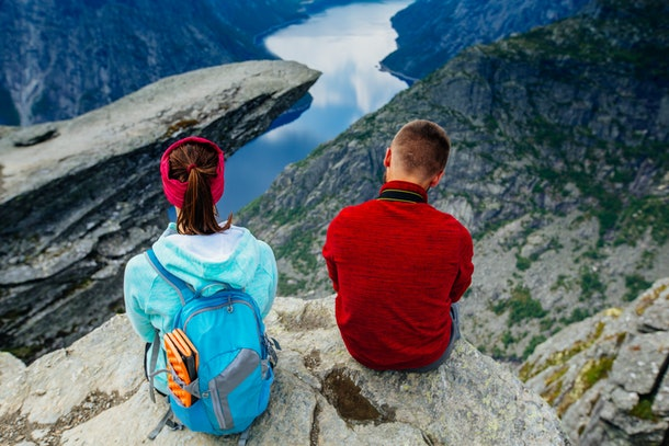 Back of couple relaxing against amazing nature view over view on Trolltunga. Location: Scandinavian Mountains, Norway, Stavanger. Artistic picture. The feeling of complete freedom