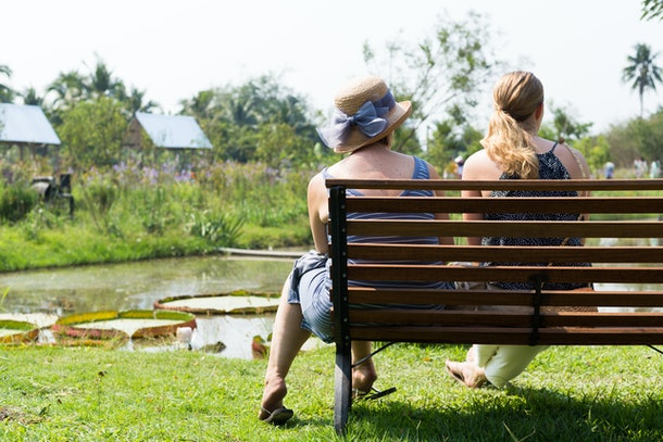 Back of couple women's sitting together on a bench in a park.
