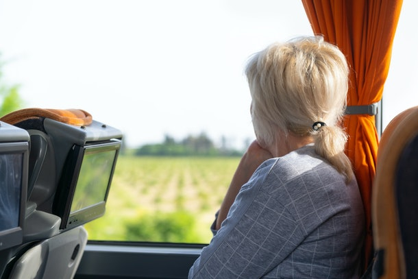 Woman looking out of the window of a coach or train watching the passing countryside as she travels on summer vacation