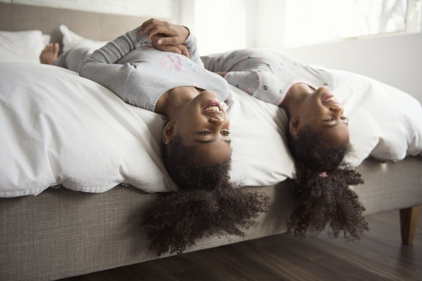 The Two smiling little african american girls on bed at home heads leaning over side of bed