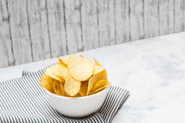 Potato chips in a bowl with white wooden vintage backdrop