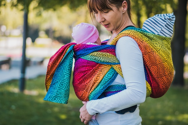 Beautiful happy young mother with two babes in carrier in park. Mom walking with twins infant in baby carrier. Happy mother carrying her children by ergonomic baby carrier.