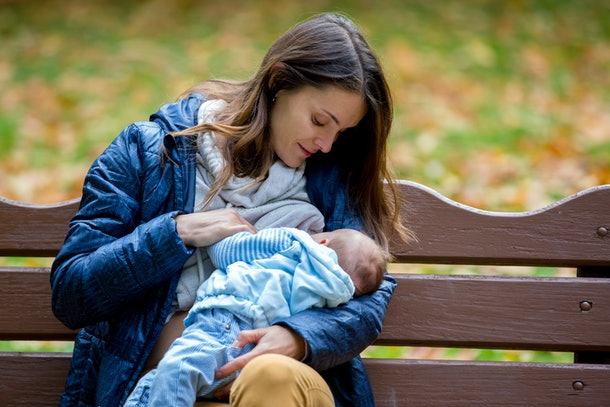 Young mother, breastfeeding her newborn baby boy outdoor in the park, autumn time