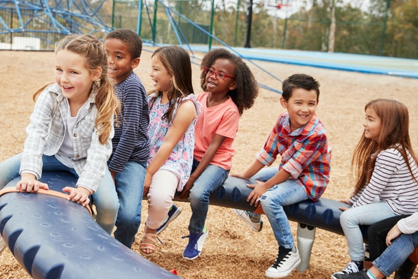Kids sitting on a spinning carousel in their schoolyard