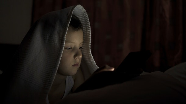 A happy boy lies in bed under a blanket and plays on a tablet in a game in the dark. The face of the child is lit by a bright monitor