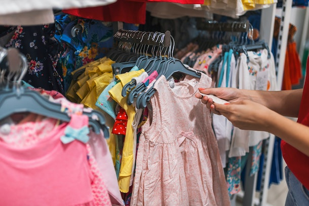 Picture showing happy woman shopping for clothes. Beautiful businesswoman buying clothes. Shopping, fashion, style and people concept. Shopaholic woman shopping clothes on sale