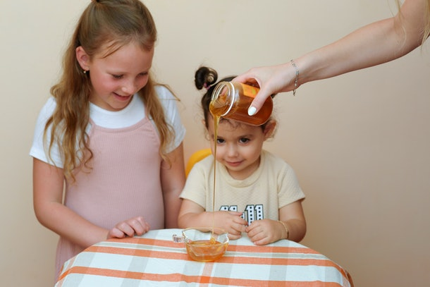 Close up portrait of two little girl with cunning tricky glance smiling looking on woman hand pouring fresh honey from jar into bowl.