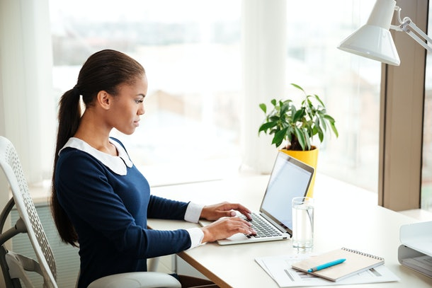 African business woman in dress sitting on armchair near the window and using laptop in office