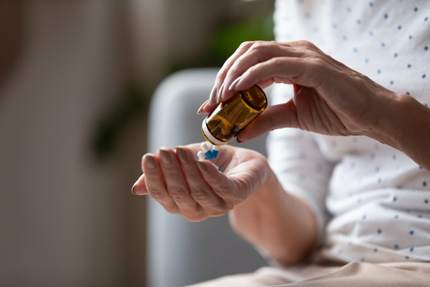 Close up mature woman taking out pills from bottle, supplements or antibiotic, older female preparing to take emergency medicine, chronic disease, healthcare and treatment concept