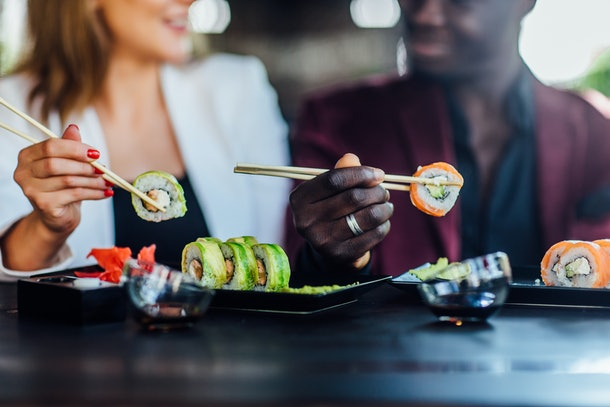 Cropped view of smiling happy couple eating sushi in restaurant, set on table.