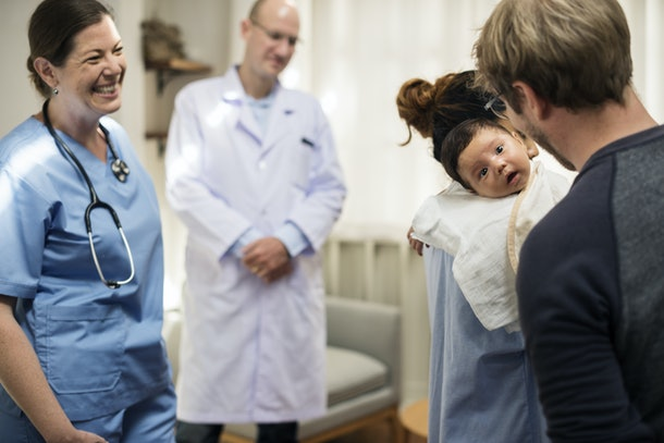 A newborn baby with family at a hospital