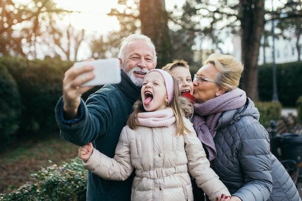 Grandparents taking selfie photo with their grandchildren in city park.