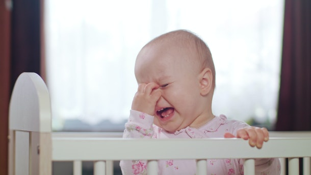 Baby's standing in a white crib at home and crying. Medium shot.