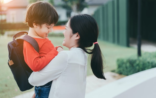 Mother get a son pupil from school after study school back to home village with satchel happy family lifestyle.