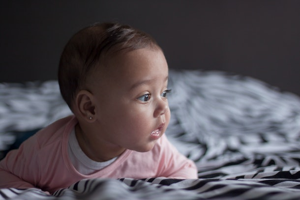 Portrait of a sweet baby girl with beautiful brown eyes with  a pink shirt lying on parents bed holding her head up