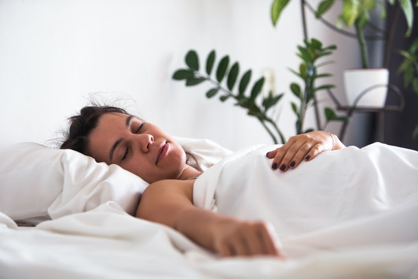 woman sleeping in bed hand close up selective focus white sheets