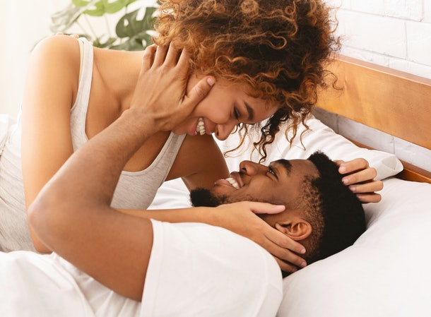 Good morning sex. Happy african-american man and woman kissing in bed, waking up in morning