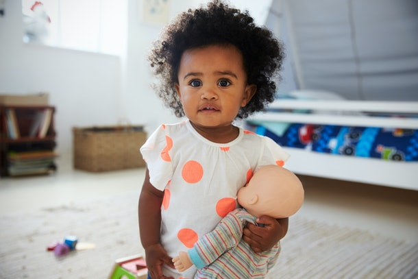 Portrait Of Baby Girl Playing With Doll In Playroom