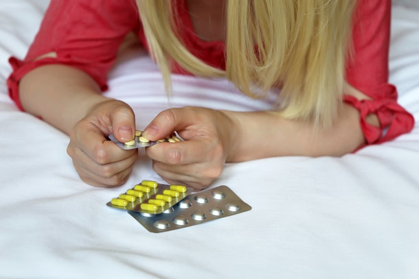 Woman with pills, female hands on the bed with a blister pack of tablets. Blonde girl taking medication, concept of illness, vitamins for beauty, treatment of cold and flu, dieting, sleeping pill