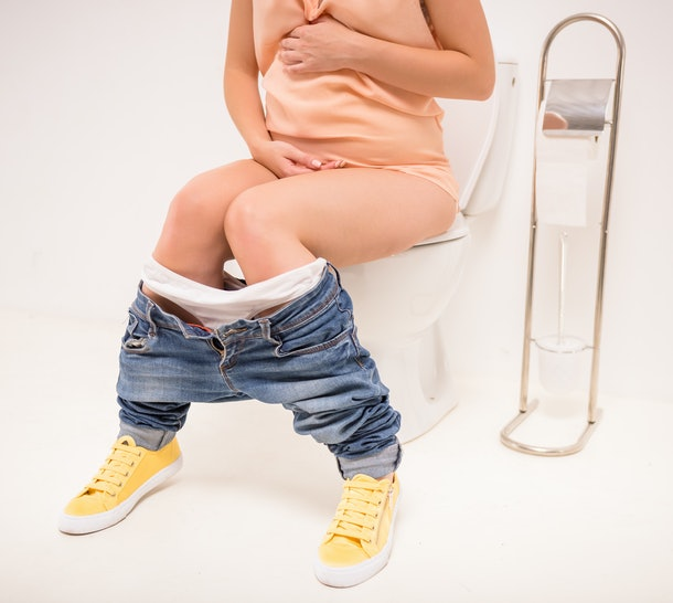 Young pregnant woman use the toilet, isolated on a white background