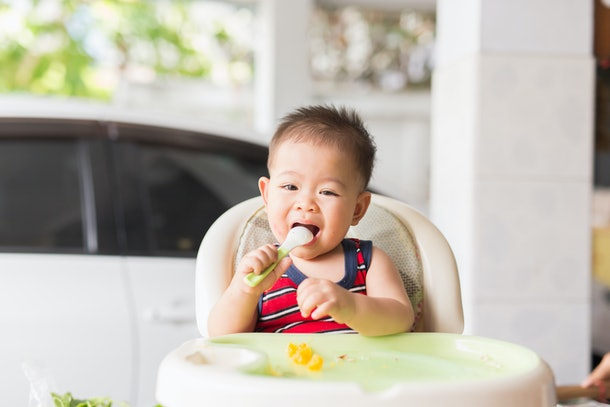 the baby learns to eat by himself. he can use spoon well. so he is very happy (focus at his face)