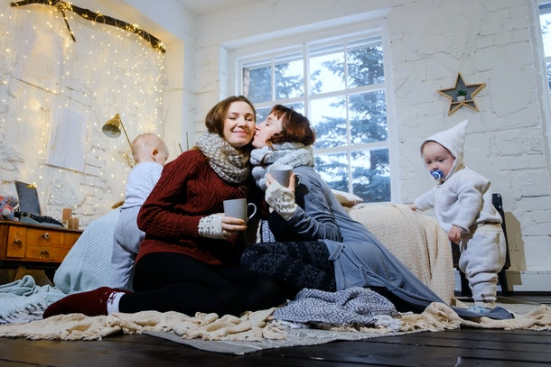 Unconventional family. Happy mom lesbians play in the morning with their sons. Christmas morning. Christmas concept.