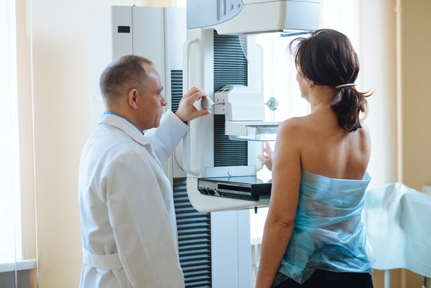 Male octor Standing Assisting Female Patient Undergoing Mammogram X-ray Tes