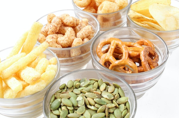 Assorted salty snacks and crisps. Closeup of junk food for party