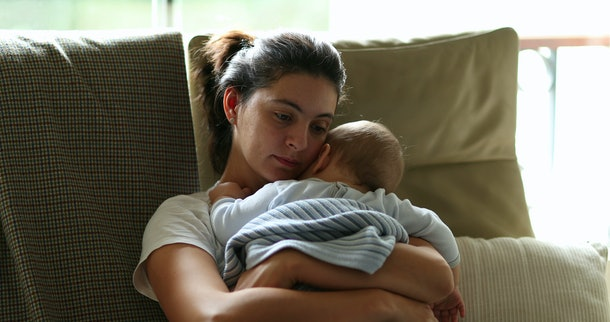 Tired mother holding and caring for baby infant on couch. Exhausted mom falling asleep, candid and authentic