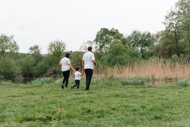 Happy family: mother father and child son on nature on sunset. Mom, Dad and kid laughing and hugging, enjoying nature outside. Sunny day, good mood. concept of a happy family