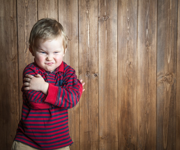 Very angry little boy. Cute toddler child is looking at camera. On wooden background. Space for text.