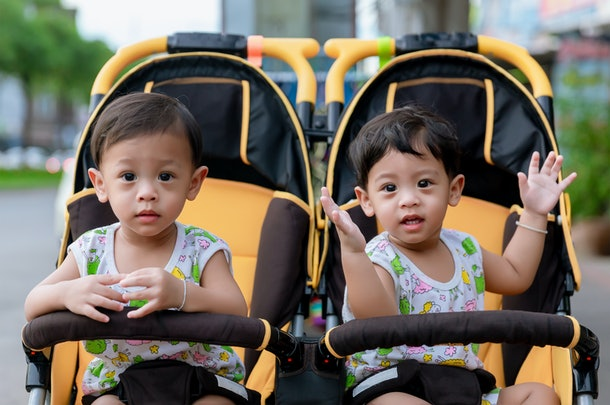 Two brothers sit in a stroller. Adorable twin baby boys sitting in stroller and smiling happily. Childhood emotions. Nursing twins