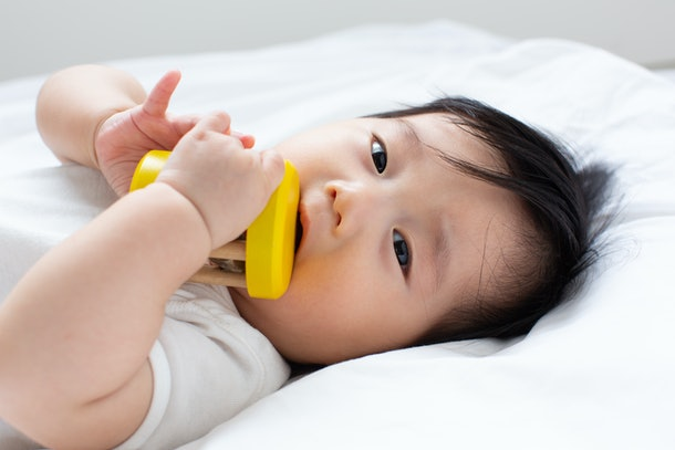 asian little baby sucking baby rattle