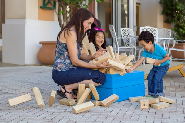 The jumbling tower falls apart while everyone is laughing and trying to keep it from going everywhere on the patio. Mom spends quality time playing with her two kids outside.