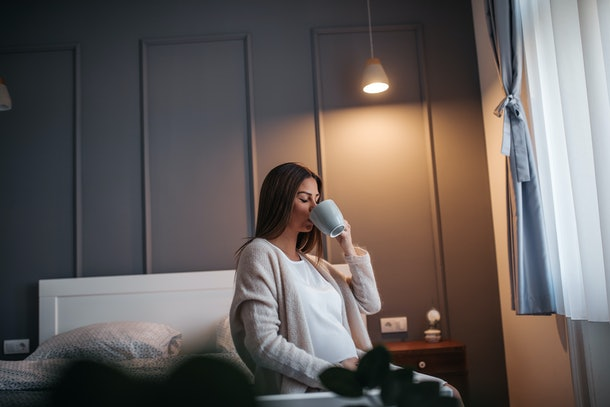 Pregnant woman drinking tea in the bedroom
