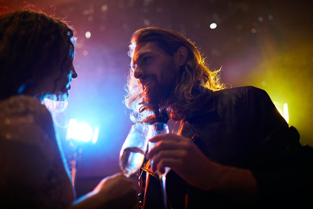 Content hipster young bearded guy with flute talking to charming lady while flirting with her in nightclub