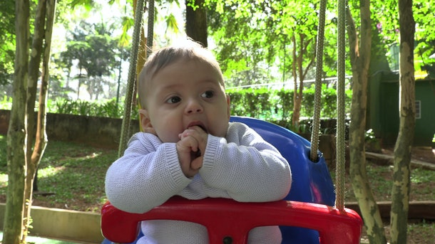 Baby boy at playground park swing outdoors