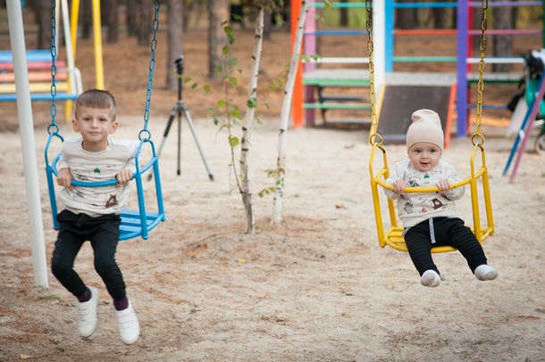 Two baby boys swinging on a swing in the park.