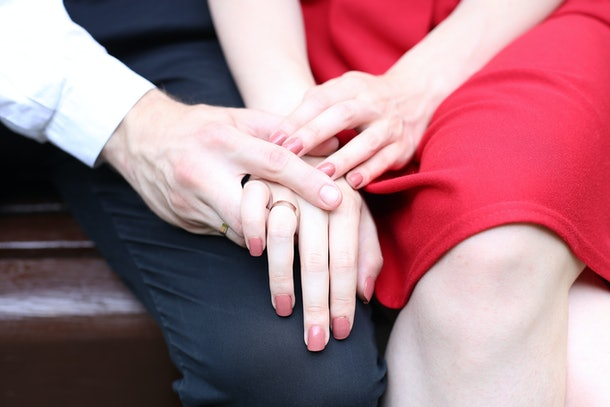 Woman in red dress and a man in love are holding their hands with golden rings