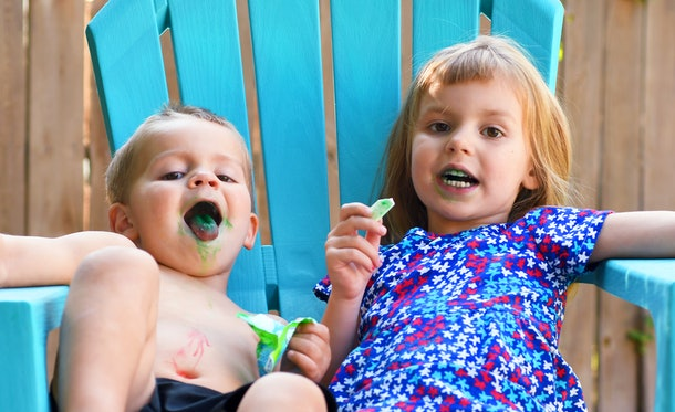 Two toddlers eating candy with blue tongues