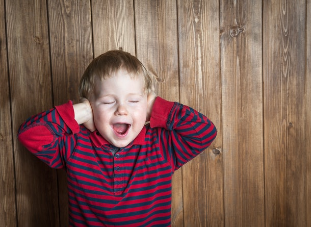 Cute boy shouts covered his ears with his hands. Stressed child. boy shouting on wooden background. Space for text. sad and unhappy child. Upset toddler boy. problem child with head in hands
